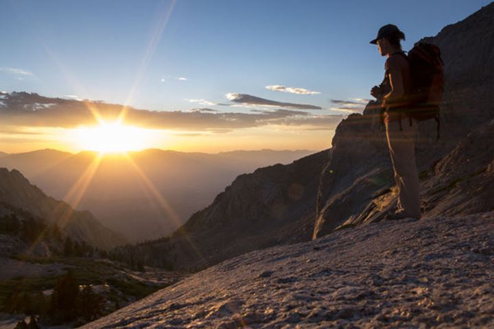 A female stands and watches the sunrise over the Eastern Sierras in California.