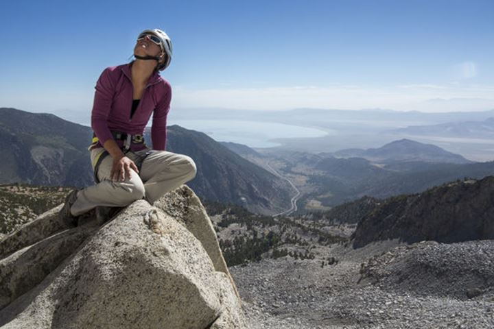 A female rock climber sits above the small town of Lee Vining, outside of Yosemite National Park, peering up towards the Third Pillar of Dana.