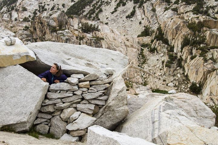 A female peaks out the window of a rock structure shelter, staring up at the Incredible Hulk in the eastern sierras of California.
