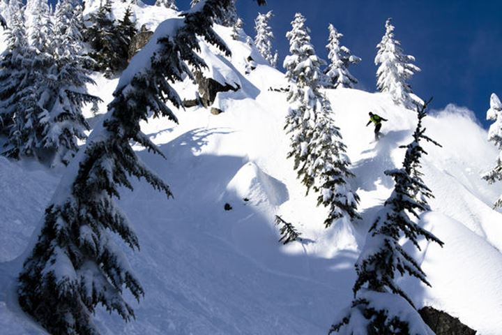 A male snowboarder in green jacket rips a turn while riding Cowboy Ridge in the side country of Steven???s Pass in Skykomish, Washington on February 27, 2012.
