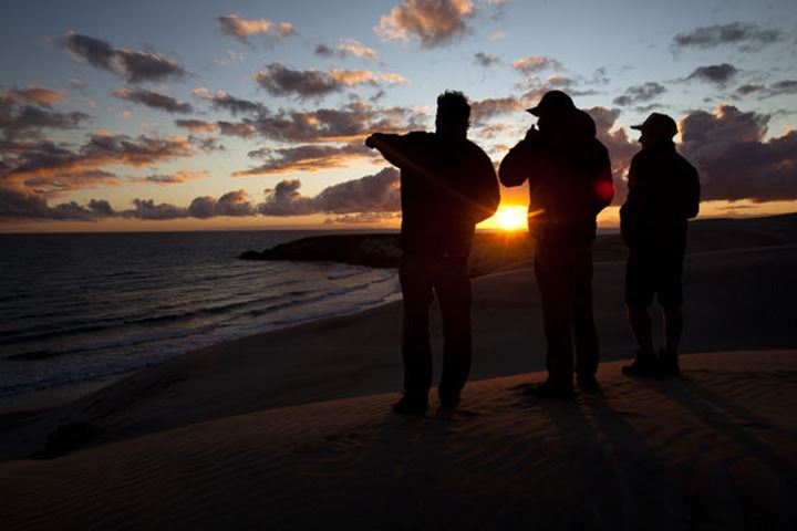 Three male surfers check the surf conditions at sunset during a surf trip in Central Baja, Mexico on December 17, 2011.
