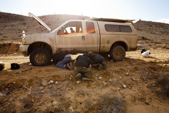 Three male surfers repair a flat tire during a surf trip in Central Baja, Mexico on December 17, 2011.
