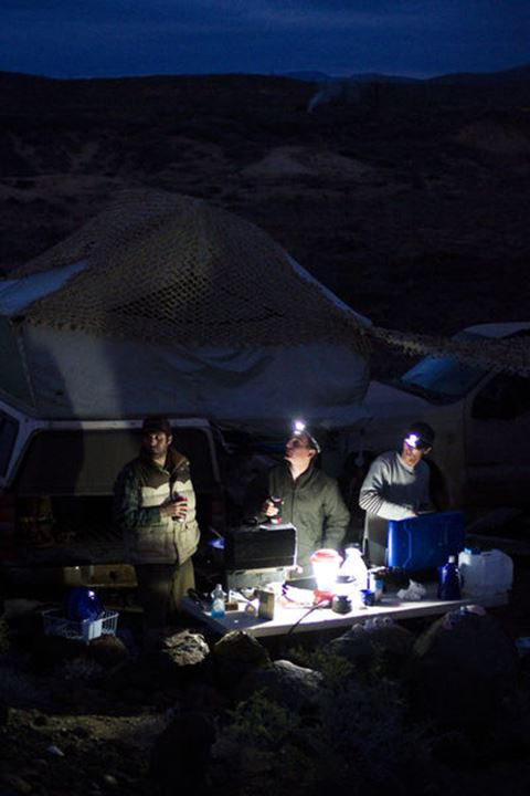 Three male surfers cook dinner at their remote campsite in Central Baja, Mexico on December 16, 2011.