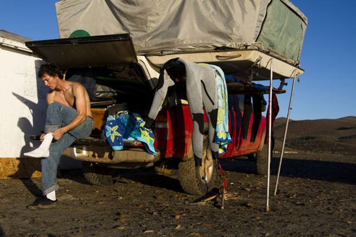 A male surfer sitting on the back of a truck puts his clothes back on after surfing in Central Baja, Mexico on December 14, 2011.