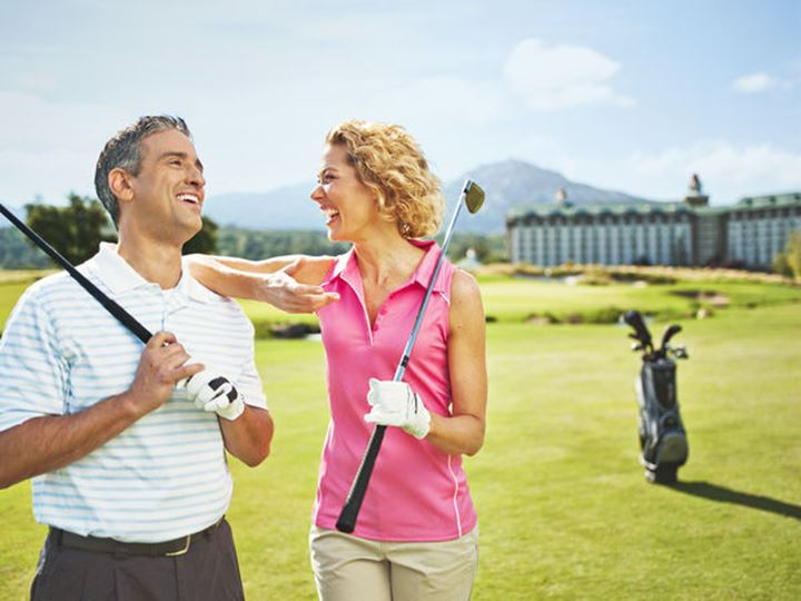 A couple enjoying a sunny afternoon practicing in a golf course