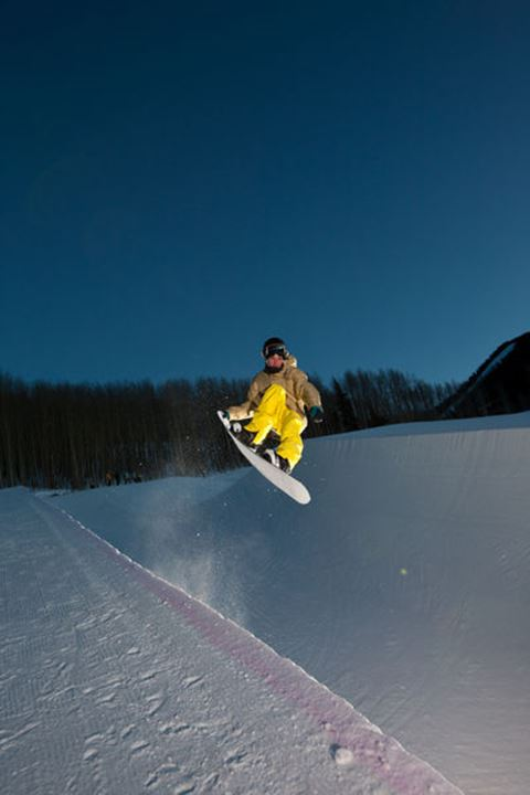 A snowboarder launches out of a half-pipe and into the twilight sky