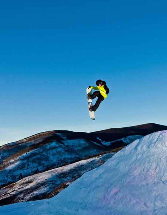 A snowboarder launches into the twilight sky