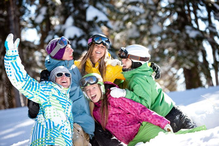 A playful group of snowboarders enjoy an unbridled moment of fun in the snow