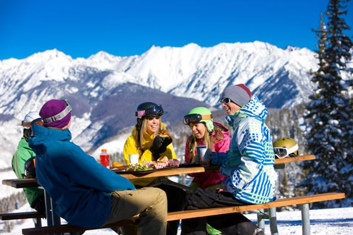 A group of snowboarders enjoy a light-hearted lunch at the top of a mountain resort