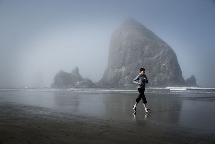 A woman jogs on the beach during the morning in Cannon Beach, Oregon.