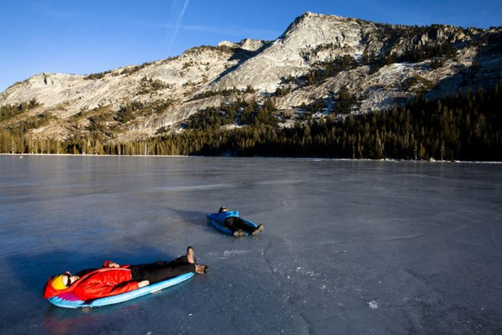 Two male ice climbers kick back in pool rafts on Tenaya Lake in Tuolumne Meadows, California on January 13, 2012.  To access Tuolumne Meadows the climbers drove up The Tigoa Pass, which has not been