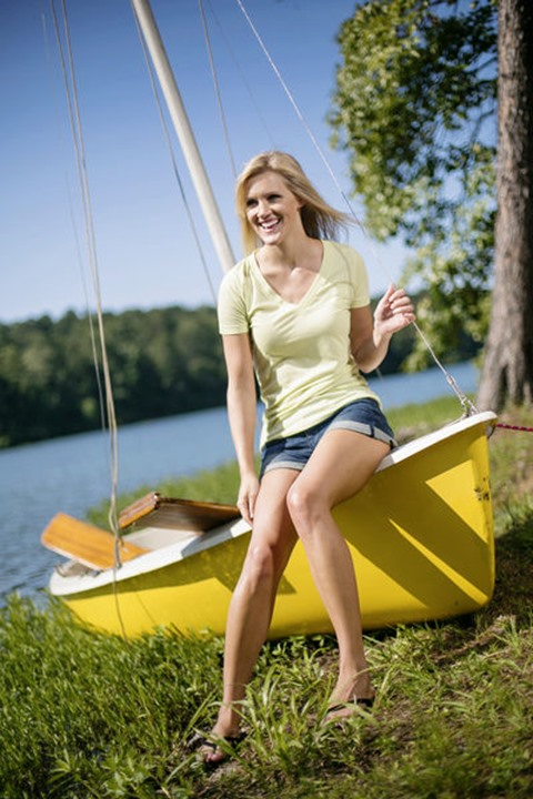 A young woman smiles while sitting on the edge of a yellow sailboat after sailing on a lake in Alabama.