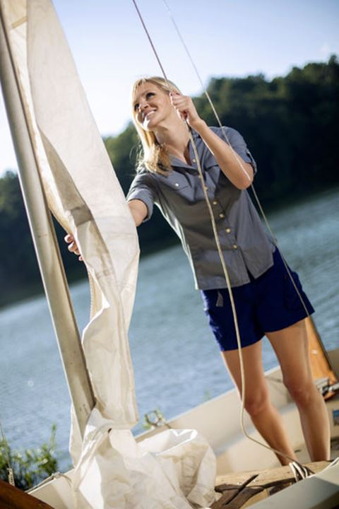 A young woman lowers the sails after finishing sailing on a lake in Alabama.