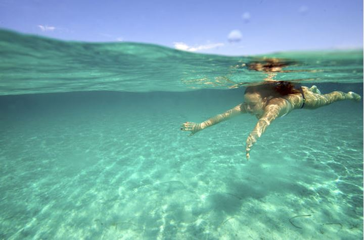 Underwater view of a woman swimming in the sea in Sardinia, Italy