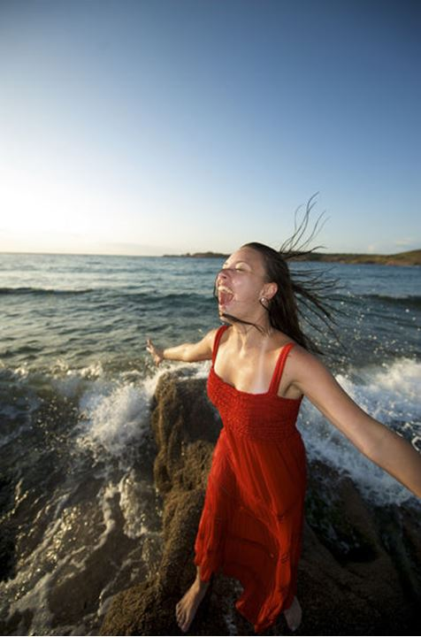 Pretty girl splashing by the wave on the beach at sunset time in Sardinia, Italy