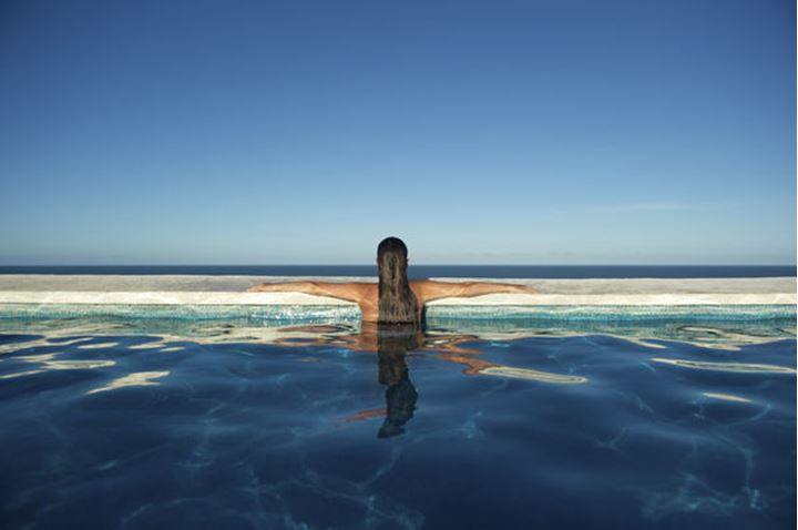 Young Brazilian woman relaxing in a swimming pool with sea view in Arraial d'Ajuda, Bahia, Brazil.
