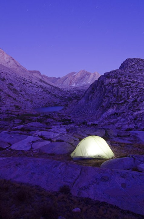 A tent is illuminated at dusk near Cirque Pass on the Sierra High Route, CA. The Sierra High Route is a 195 mile mostly trackless path through the Sierra Nevada high country.