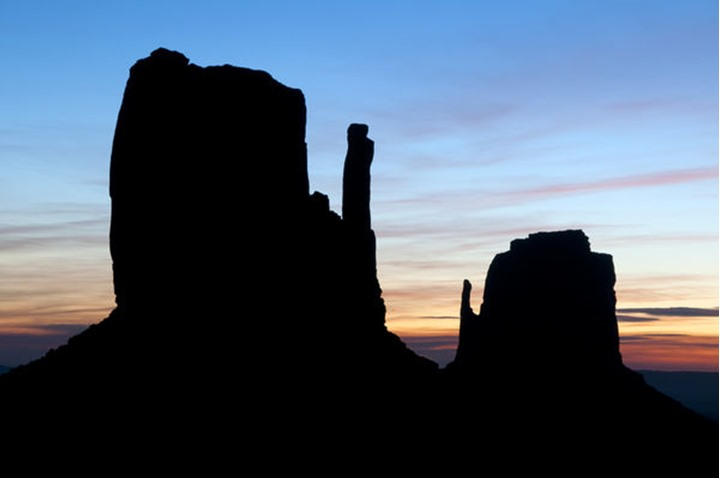The famous Mittens are silhouetted at sunrise in Monument Valley, AZ.  Monument Valley is located in the four corners area of the United States and is part of the Navajo Nation.