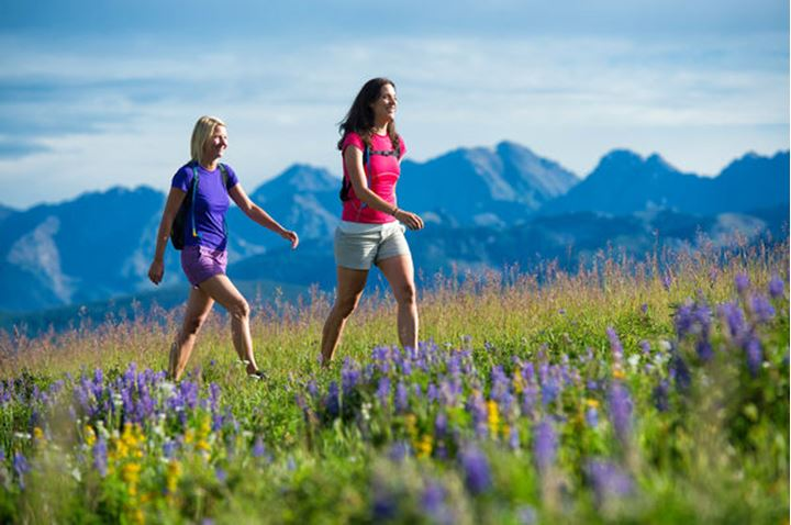 Two female hikers on a mountain top.