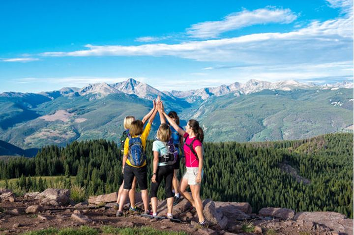 A group of women celebrate at the top of a mountain.