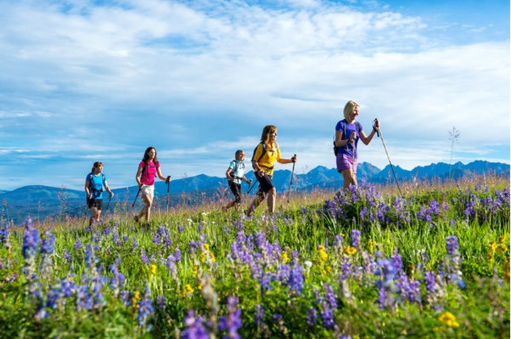 A women's hiking group heads up a mountain-top hiking path.
