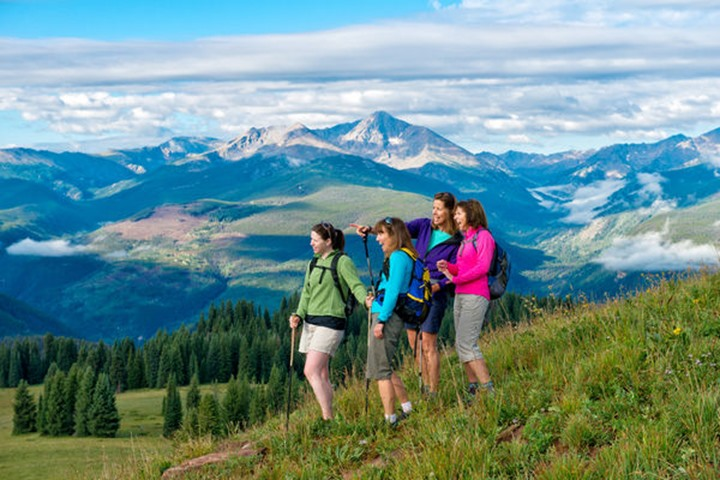 A group of women hikers soak in the views at the top of a mountain.