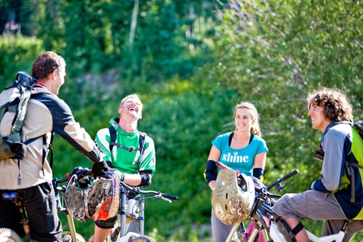 A group of young downhill mountain bikers swap stories  and laugh following a fun day of riding.
