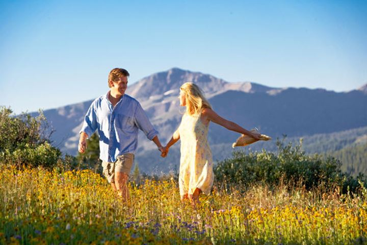 A happy couple enjoy the beauty of an early an morning hike in a field high atop a Colorado mountain.