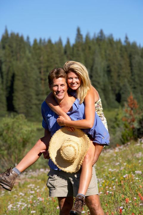 A happy couple smile as they play in a field of wild flowers.
