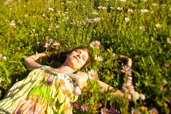A woman smiles as she lays in a field of  flowers on a warm sunny Summer morning