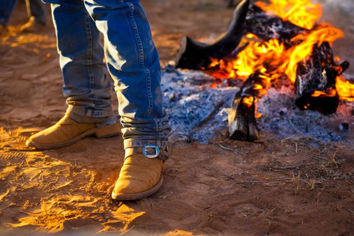 A cowboy stands next to a morning campfire