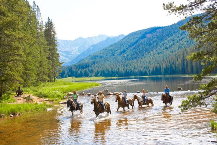 A group of  horseback riders cross a stream during a ride in the high mountain trails of Piney Lake near Vail, Colorado.