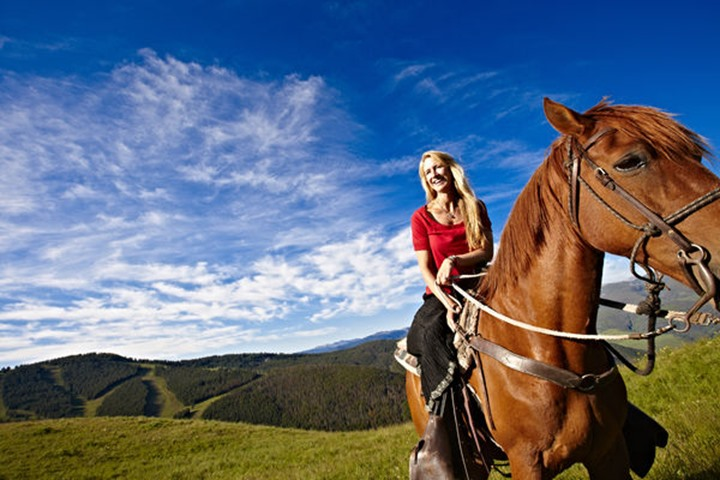 A woman laughs as she enjoys a moment on a horseback ride a high alpine mountain Summer meadow