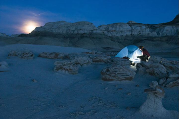 A male hiker settin up his tent at moonrise in the complex sandstone rock formations at Bisti Badlands, Farmington, New Mexico.