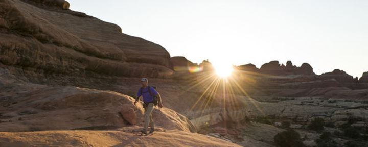 A man hiking along sandstone trail at sunset in the Needles District of Canyonlands National Park, Monticello, Utah.