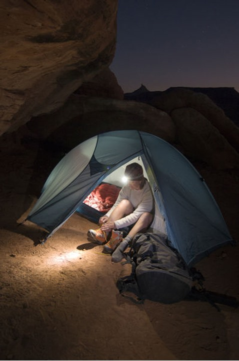 A woman camping at night in a tent with a headlamp in Indian Creek Canyon, Monticello, Utah.