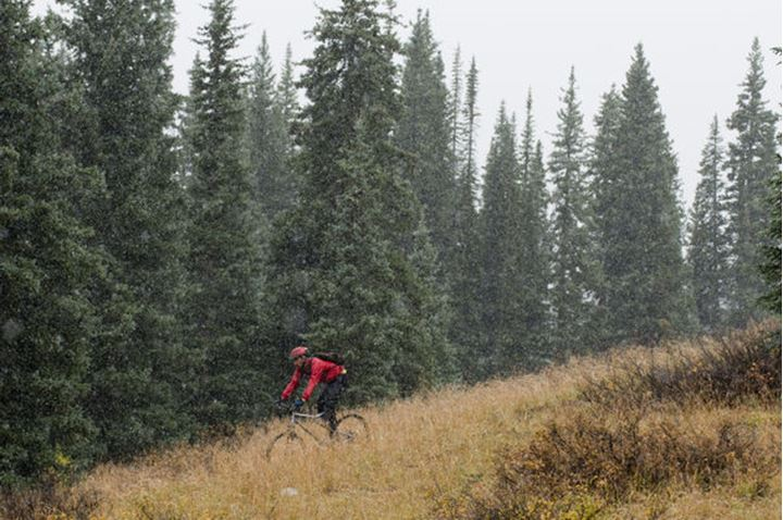A man mountain biking in a snow storm near Molas Pass in the San Juan National Forest, Silverton, Colorado.