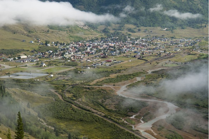 The fog filled valley of the Town of Silverton with the Animas River and the Durango to Silverton Narrow Gauge Railroad tracks, Silverton, Colorado.
