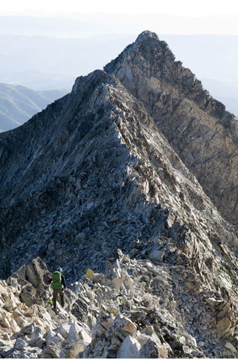 A man descending the Knife Edge, a challenging section on Capitol Peak in the Maroon Bells Wilderness, White River National Forest, Aspen, Colorado.