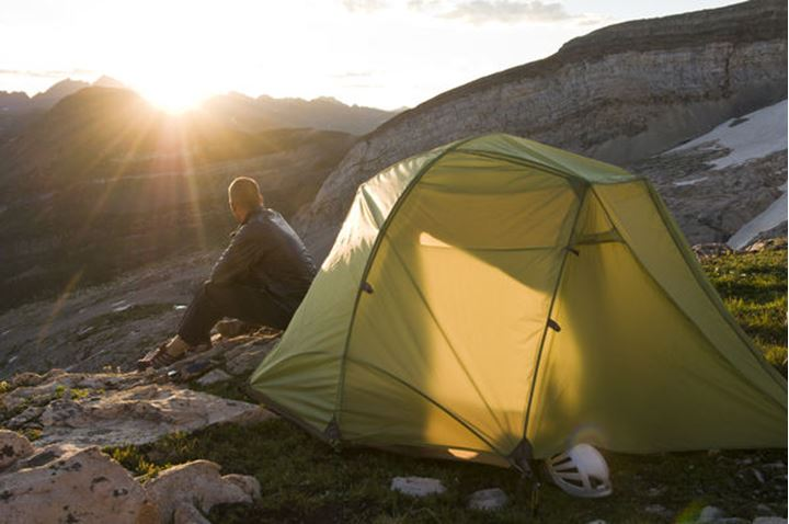 A man enjoying a sunrise next to his tent while camping below Treasure Mountain in the White River National Forest outside of Marble, Colorado.