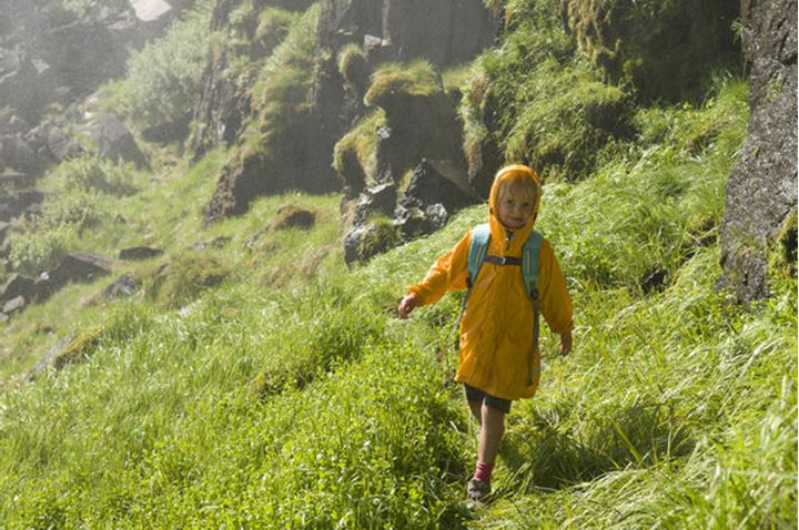 A young girl hiking a grassy slope which is getting wet from the spray of Clear Creek Falls, Rio Grande National Forest, Creede, Colorado.