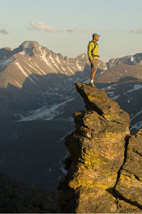 A man on the top of a slender spire at the Rock Cut with Long's Peak in the background, Trail Ridge Road, Rocky Mountain National Park, Estes Park, Colorado.