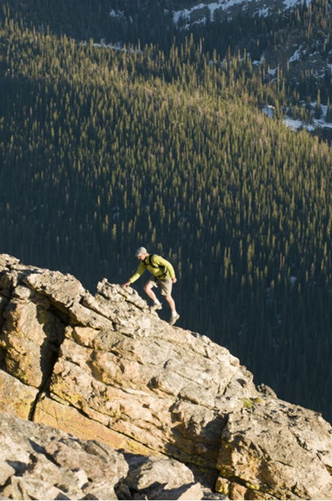 A man hiking along a rocky ridge at the Rock Cut on the Trail Ridge Road in  Rocky Mountain National Park, Estes Park, Colorado.