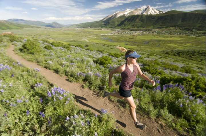 A woman trail running past wildflowers on the Lupine Trail in Crested Butte, Colorado.