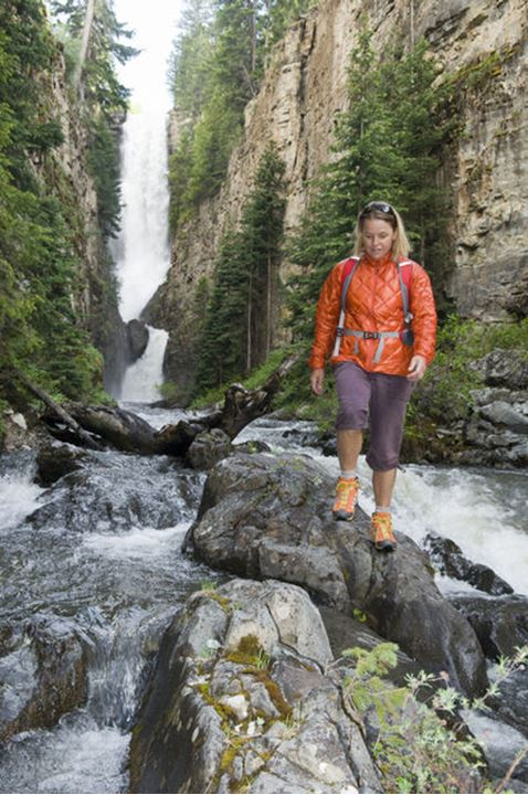 A woman stepping along rocks in a stream, while hiking below Ames Falls, Ames, Colorado.