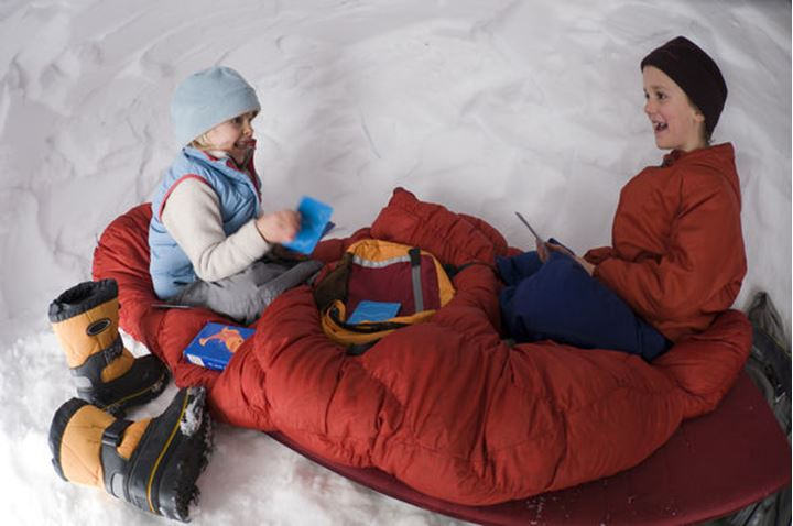 Two young girls sitting on a sleeping bag and playing cards inside a snow cave on Molas Pass, Silverton, Colorado.
