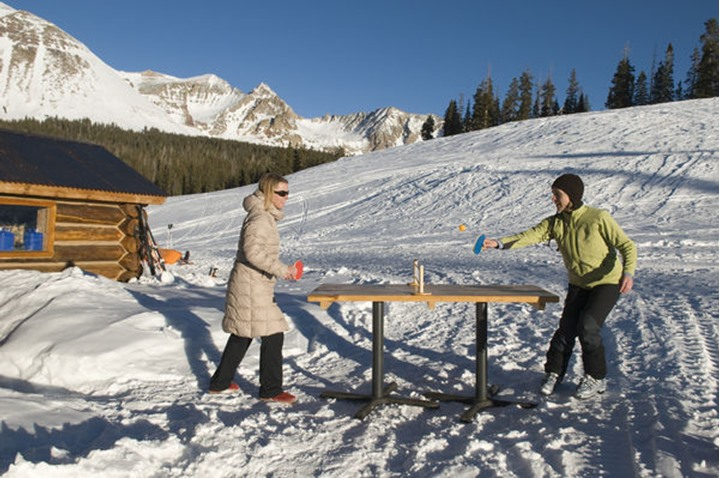 Two women playing outdoor ping pong next to a backcountry ski hut on Lizard Head Pass, Telluride, Colorado.