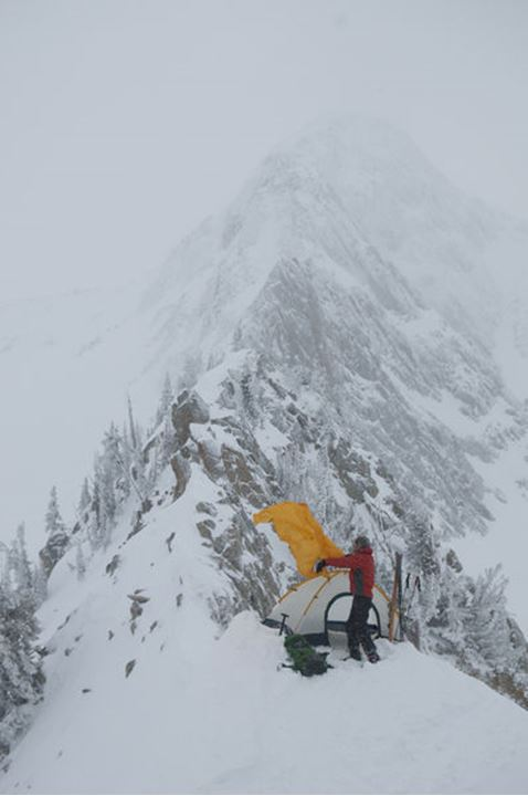 A man pitching a tent on a stormy ridgeline below the Pfeifferhorn, Red Pine Canyon, Wasatch National Forest, Salt Lake City, Utah.