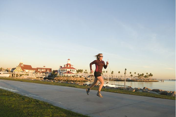 A woman on an evening run along the Long Beach Boardwalk, Long Beach, California.