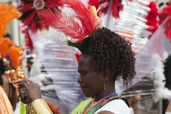England, London, Notting Hill Carnival, West Indian Woman Taking Photograph